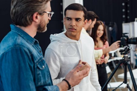 selective focus of handsome assistant looking at art director in glasses