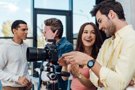 Photo pour Focus sélectif de collègues heureux se tenant près de l'appareil photo numérique - image libre de droit