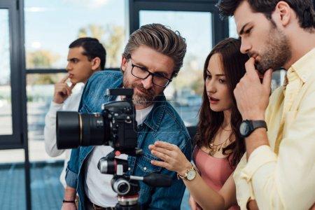 selective focus of art director looking at digital camera near assistants