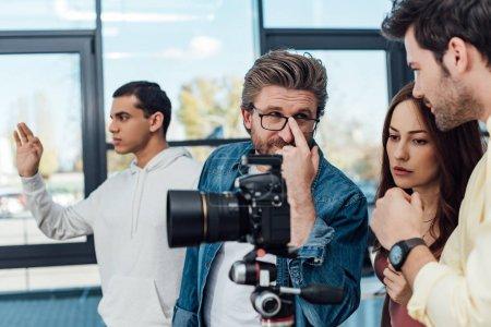 Photo pour Foyer sélectif du directeur artistique touchant des lunettes et regardant assistant près de l'appareil photo numérique - image libre de droit