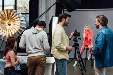 Photo pour Foyer sélectif du directeur artistique dans les lunettes en regardant le photographe près des assistants et le modèle - image libre de droit