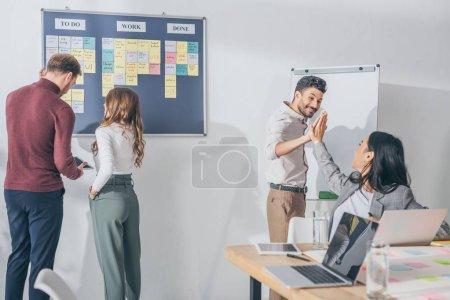 Photo pour Heureux mixte race homme donnant haute cinq à asiatique femme d'affaires près de scrum maîtres - image libre de droit