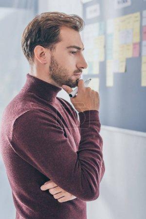 Photo pour Vue de côté de l'homme d'affaires coûteux tenant stylo marqueur - image libre de droit