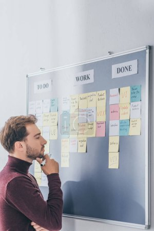 Photo for Side view of handsome scrum master thinking near board with sticky notes and letters - Royalty Free Image