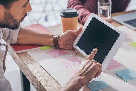 Photo pour Foyer sélectif de barbu mixte homme d'affaires pointant avec le doigt à la tablette numérique avec écran blanc - image libre de droit