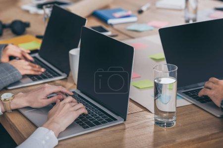 Photo pour Vue recadrée des maîtres de mêlée à l'aide d'ordinateurs portables avec écran blanc dans le bureau - image libre de droit