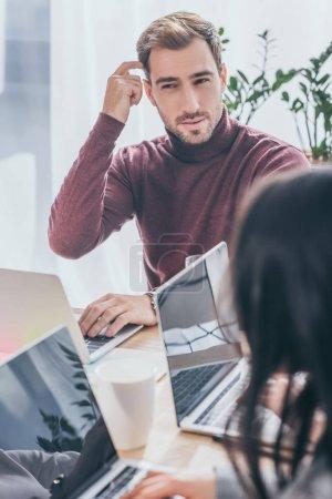 Photo pour Foyer sélectif de beaux hommes d'affaires pensant près des ordinateurs portables - image libre de droit