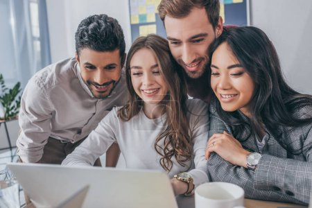 Photo pour Des hommes et des femmes d'affaires multiculturels souriants regardant un ordinateur portable dans leur bureau - image libre de droit