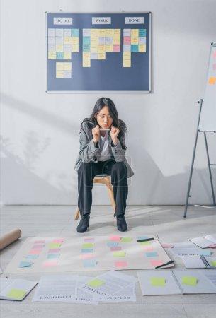 Photo pour Manoeuvrier asiatique pensif assis sur une chaise et regardant des notes collantes - image libre de droit