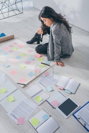 Photo pour Belle asiatique scrum maître assis sur sol près de documents avec lettres - image libre de droit