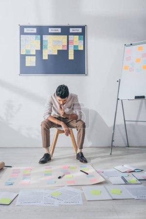 Photo pour Mannequin métis pensif assis sur une chaise et regardant des notes collantes - image libre de droit
