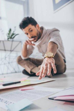 Photo pour L'accent sélectif d'un homme d'affaires métis assis la main tendue près de notes collantes sur le sol - image libre de droit