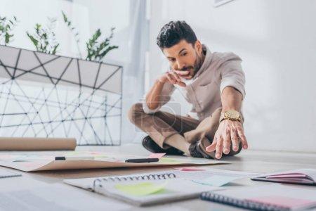 Photo pour L'accent sélectif d'un homme d'affaires métis pensif assis la main tendue près de notes collantes sur le sol - image libre de droit