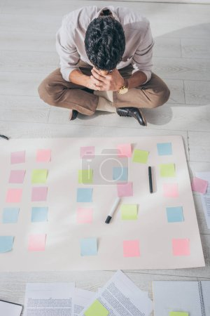 top view of mixed race scrum master sitting on floor near sticky notes