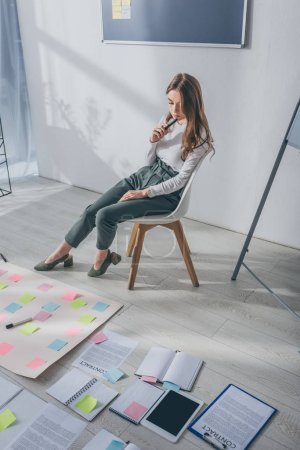 attractive businesswoman sitting on chair near sticky notes on floor