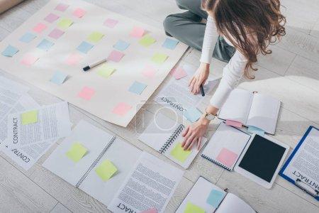 Photo pour Vue recadrée de femme d'affaires assise sur le sol près d'une tablette numérique avec écran vierge et notes collantes - image libre de droit