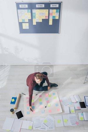 Photo pour Vue du dessus du stylo marqueur scrum master tenant près des notes collantes assis sur le sol - image libre de droit