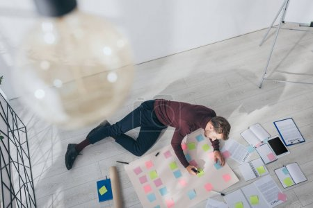 Photo pour Top view of scrum master holding marker pen near sticky notes while lying on floor - image libre de droit