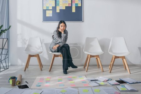 Photo for Beautiful asian scrum master sitting on chair near gadgets and sticky notes - Royalty Free Image