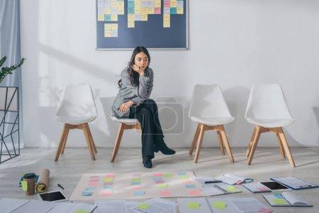 Photo pour Magnifique maître de mêlée asiatique assis sur une chaise près de gadgets et de notes collantes - image libre de droit