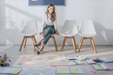 Photo for Attractive scrum master sitting on chair near sticky notes on floor - Royalty Free Image