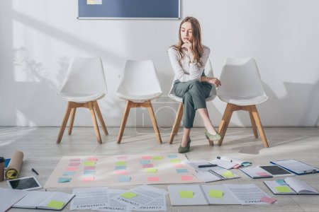 Photo for Attractive scrum master sitting on chair near sticky notes and gadgets on floor - Royalty Free Image