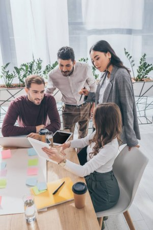 multicultural coworkers looking at digital tablet in office