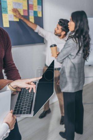 Photo pour Vue recadrée d'une femme d'affaires pointant du doigt un ordinateur portable près de collègues multiculturels - image libre de droit