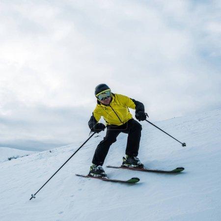 Photo pour Sportsman tenant des bâtons de ski en skiant sur pente blanche - image libre de droit