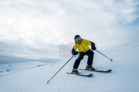 Photo pour Sportsman tenant des bâtons de ski en skiant sur neige blanche - image libre de droit