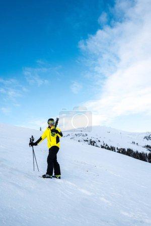 Photo pour Skieur avec bâtons de ski debout sur la neige blanche à l'extérieur - image libre de droit