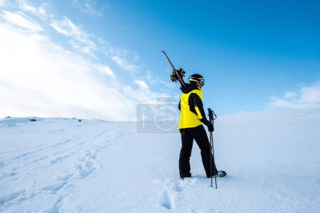 Photo for Sportsman in helmet standing with ski sticks on slope in wintertime - Royalty Free Image