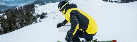 Photo for Panoramic shot of sportsman in helmet skiing in wintertime - Royalty Free Image