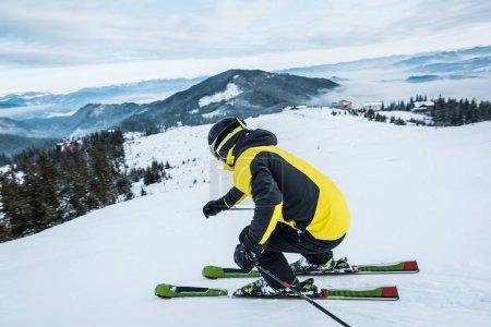 Photo pour Sportif en casque ski en montagne - image libre de droit
