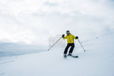 Photo for Active sportsman in helmet and goggles skiing on slope in wintertime - Royalty Free Image