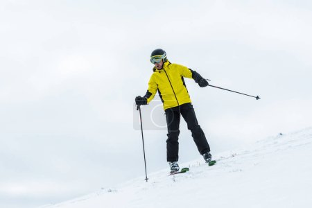 Photo for Skier in helmet holding ski sticks and skiing on slope in wintertime - Royalty Free Image