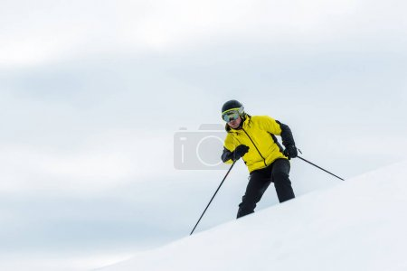 Photo for Skier in helmet holding sticks and skiing on slope in winter - Royalty Free Image