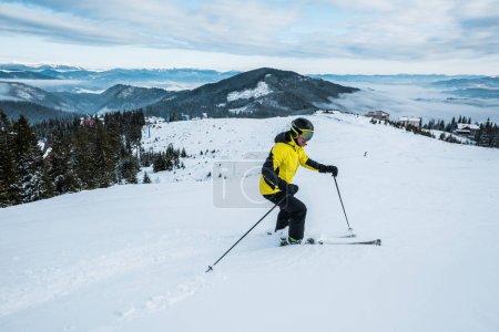 Photo pour Sportif tenant des bâtons de ski pendant le ski en hiver - image libre de droit