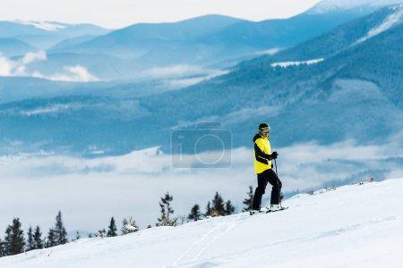Photo pour Sportif en casque tenant des bâtons et skiant sur la piste à l'extérieur - image libre de droit