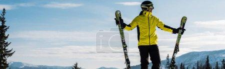 Photo pour Plan panoramique du skieur en lunettes tenant des bâtons de ski contre le ciel bleu avec des nuages - image libre de droit
