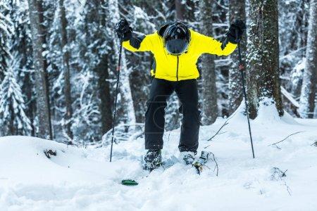 Foto de Esquiador en casco que sostiene palos de esquí mientras se encuentra cerca de los primeros en invierno. - Imagen libre de derechos