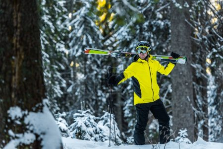 Photo for Selective focus of skier in goggles holding ski sticks and skis while standing near firs - Royalty Free Image