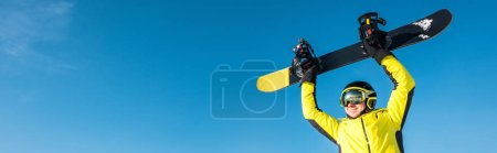 Photo for Panoramic shot of happy sportsman in helmet holding snowboard above head - Royalty Free Image