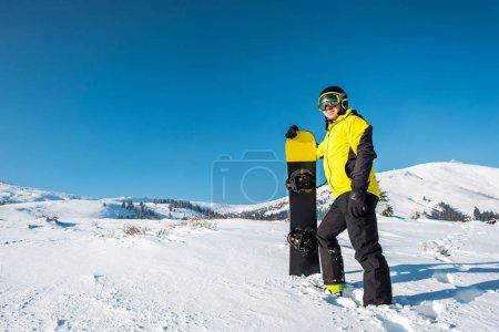 Photo pour Sportif heureux dans le casque tenant snowboard et debout sur la neige blanche dans les montagnes - image libre de droit