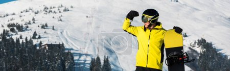 Photo pour Vue panoramique du snowboarder debout dans les montagnes et regardant loin - image libre de droit