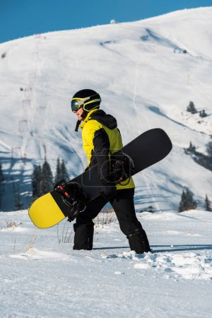 Photo for Side view of snowboarder in helmet walking in mountains with snowboard - Royalty Free Image