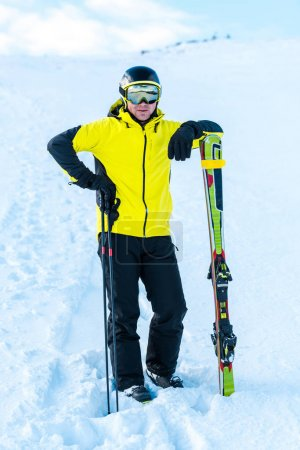 Photo for Skier in helmet standing near ski sticks on snow - Royalty Free Image
