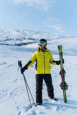 Foto de Esquiador en casco con bastones sobre nieve blanca en las montañas. - Imagen libre de derechos