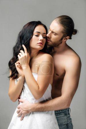 Photo pour Couple nu passionné blotti dans des draps, isolé sur gris - image libre de droit