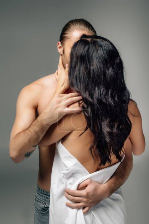 Photo for Passionate nude couple hugging and kissing in sheets, isolated on grey - Royalty Free Image
